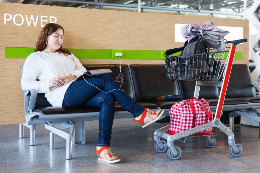 Frau wartet am Flughafen darauf, dass Ihr Tablet lädt