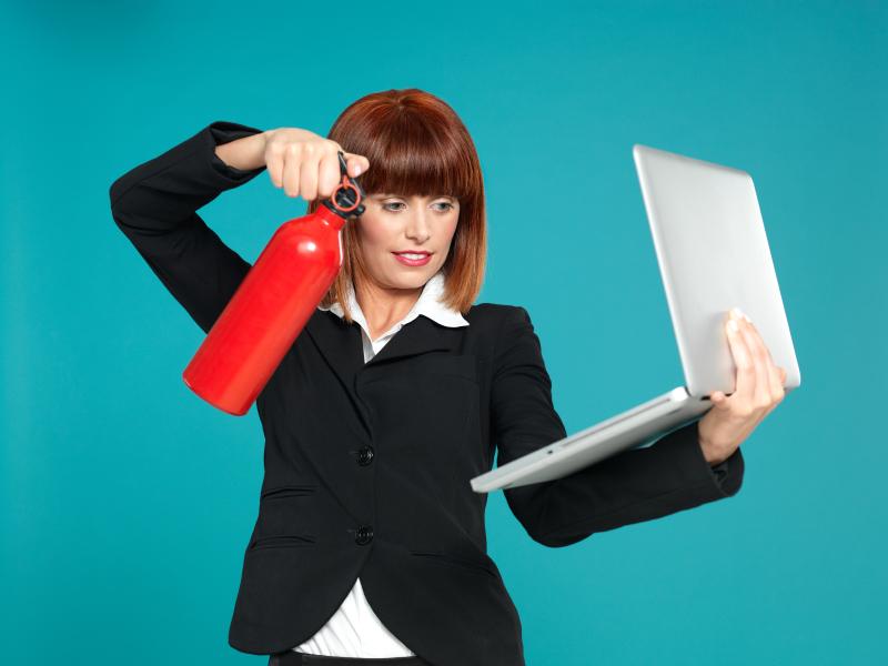 Frau mit Feuerlöscher löscht ihren Laptop